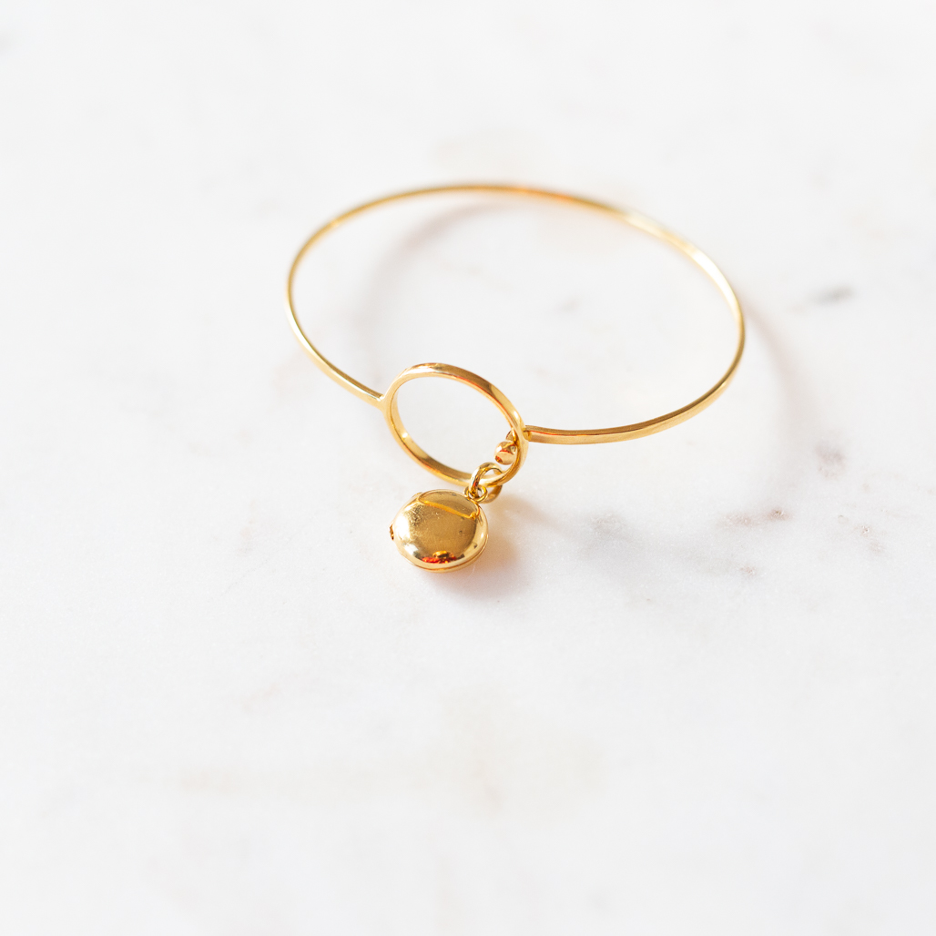 modern bracelet in gold plating with a swinging locket charm pendant where we put the photos inside for you